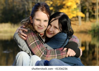 Two cute Caucasian sisters hug each other on a beautiful autumn day