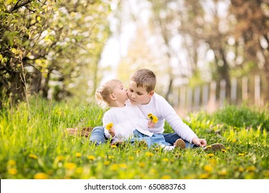 Two cute caucasian small kids, boy and girl, sitting in a grass outdoors, in a orchard, spring sunny day