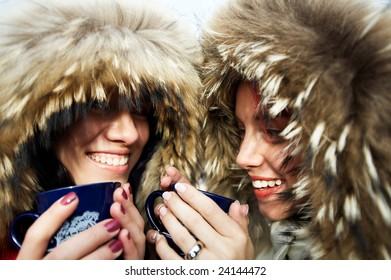 two cute caucasian women are drinking mulled wine
