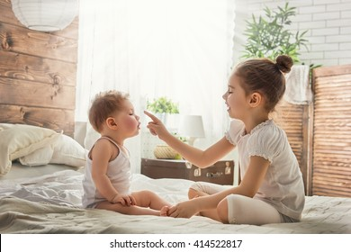 two cute child baby girls playing and having fun on the bed. loving sisters hug