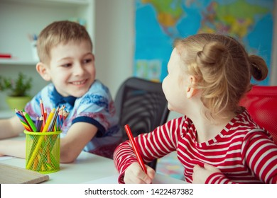 Two cute children drawing with colorful pencils at home
