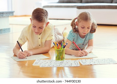 Two cute children draws with colorful pencils on the floor at home