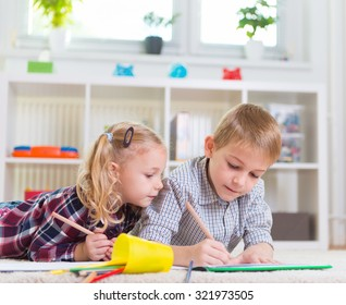 Two cute children draws on floor at home