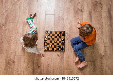 Zwei süße Kinder spielen Schach zu Hause oder im Kindergarten. Tischspiel. Junge und Mädchen der Vorschule spielen mit pädagogischem Spielzeug auf dem Boden. Spielzeug für Vorschulen und Kindergarten. Draufsicht.