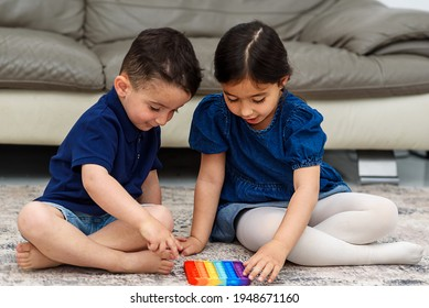 Two cute children playing with the Pop It fidget. Push pop bubble flexible fidget sensory toy provide discharge and are good for the development of kid. Soft focus.
