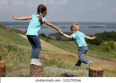 Two cute children, sister and brother, holding each other by hands and jumping down over beautiful landscape, help and support concept, friend and family, summer outdoor