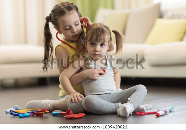 Two cute children, cute toddler girl and her older kid sister, playing doctor and hospital using stethoscope toy and other medical toys, having fun at home