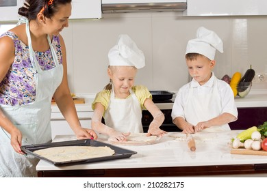 Two cute children wearing chef uniform while helping their mother to prepare the dough for baking a homemade pie, in the kitchen