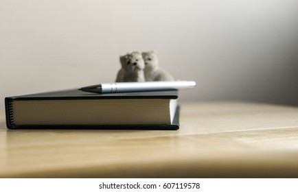 Two cute dog sitting on a notebook