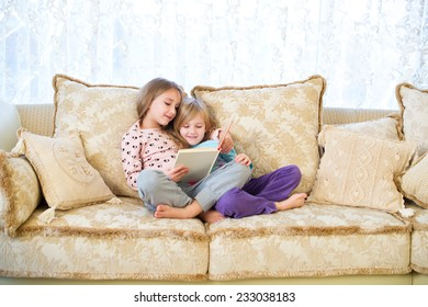 Two cute european sister girls reading a book for children and having fun in room of their home