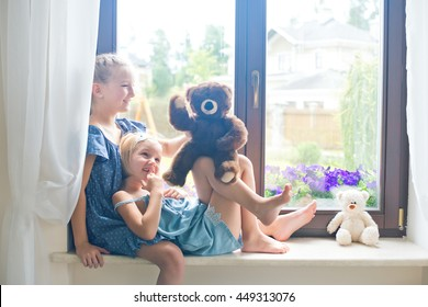 Two cute european toddler girls sitting near window at home playing teddy bears happy and funny. Colorful back yard at background