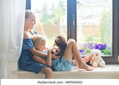Two cute european toddler girls sitting on sill near window at home playing teddy bears happy and funny. Colorful back yard at background