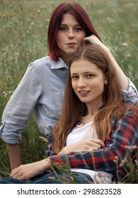 Two cute girl sitting on the grass. Vertical frame