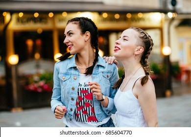 Two cute girlfriends with braids dreaming and smiling in summer time over blurred lights background outdoor at evening time in summer.