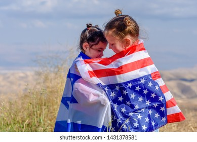 Two cute girls with American and Israel flags. Little children holding Israeli and USA flags hugging on meadow with beautiful landscape in background.