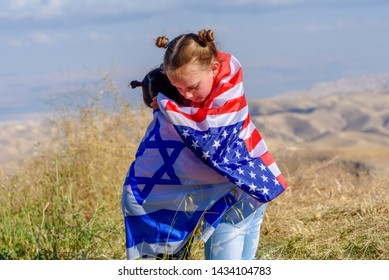 Two cute girls with American and Israel flags. Little children holding Israeli and USA flags hugging on meadow with beautiful landscape in background.Israel–United States relations.