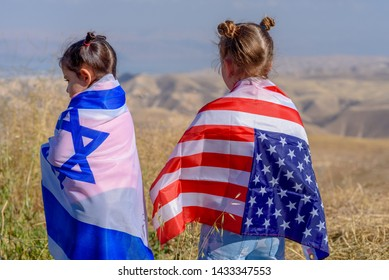 Two cute girls with American and Israeli flags.Israel–United States relations.