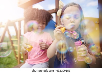 Two cute girls blowing the soap bubbles