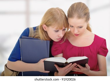 two cute girls college enthusiastically read the book
