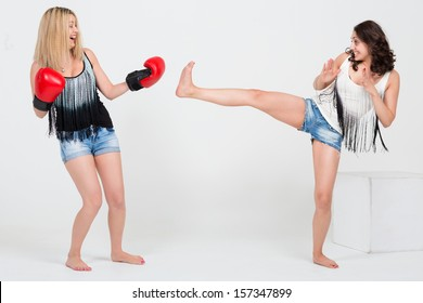 Two cute girls in denim shorts having fun, one with boxing gloves other kicks