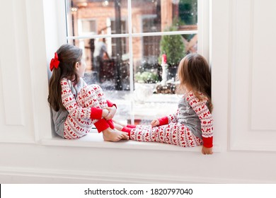 Two cute girls in pajamas sitting and looking out the window at snowy weather. Christmas moments with kids at home