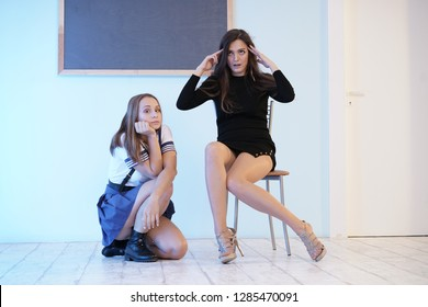 two cute girls posing at the blackboard. sexy teacher and funny student in school uniform emotionally communicate.