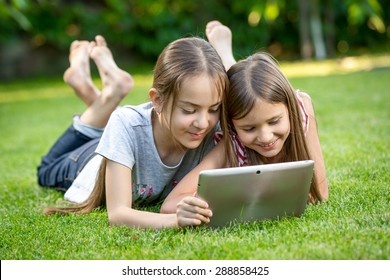 Two cute girls relaxing on grass at park and using digital tablet