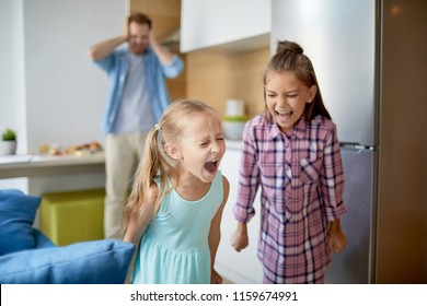 Two cute girls shouting loudly during their home play on background of their father covering ears