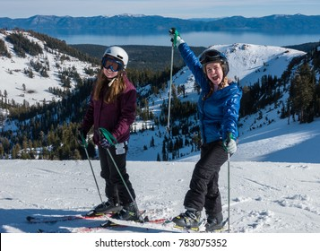 Two cute girls at the top of the ski run at Alpine Meadows Ski Resort, part of Squaw Valley Resort, in the Sierra Nevada Mountain Range of California, with a view of Lake Tahoe in the background.