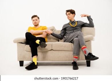 Two cute guys make a bet hand in hand sitting on a white sofa. Group of friends are sitting on a soft couch and communicates isolated on white background.