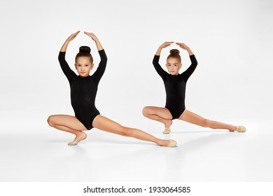 two cute gymnast child girl show athletic skills on white studio background