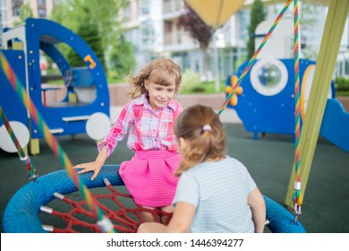 Two cute happy little girls, kids having fun on swings at playground in the big city