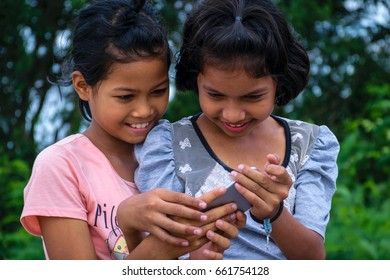 Two cute happy smiling beautiful girl playing smartphone on bicycle with smile and happy expression