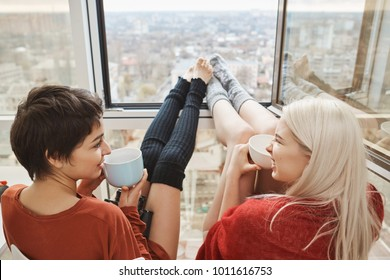 Two cute and happy woman sitting on balcony, drinking coffee and chatting with stretched legs that leaned on window. Girlfriends talk about plans for today, wanting to skip work and stay home