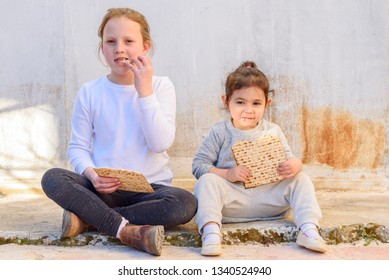 Two cute jewish girl eating matzah outdoor rural background.