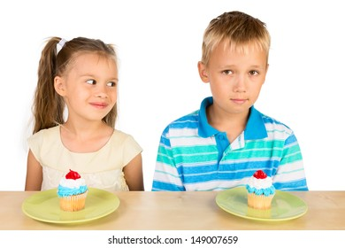 Two cute kids: a boy and a girl are sitting at the table with two delicious cupcakes in front of them, isolated