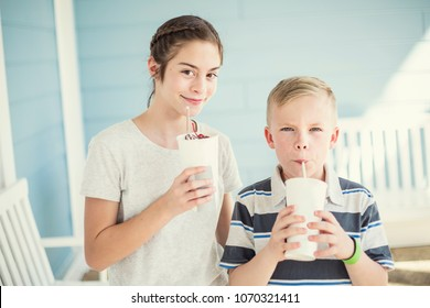 Two Cute kids drinking milkshakes or flavored drinks together outdoors on a warm summer day. Enjoying some cool liquid refreshment