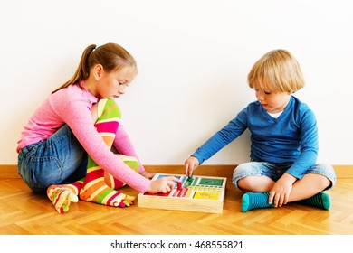 Two cute kids, little brother and his big sister playing board games at home, wearing funny socks