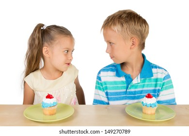 Two cute kids are looking at each other in a friendly way with two delicious cupcakes on a table in from of them, isolated