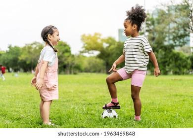 Zwei süße kleine afrikanische Amerikaner spielen Fußball zusammen auf dem Gras an einem sonnigen Sommertag, Sport für Gesundheit. Sport- und Kinderkonzept.