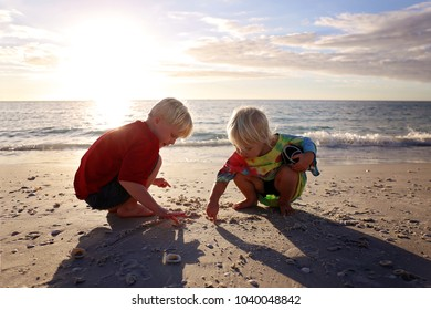 Two cute little blonde children, a boy and a girl, are playing at the beach by the ocean, drawing in the sand, at sunset.