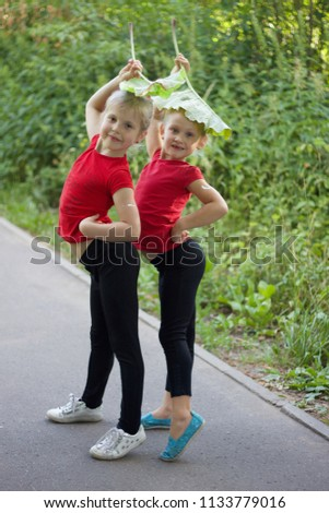 e1b221552 Two cute little blonde girls in the red T-shirts with the burdock leaves on