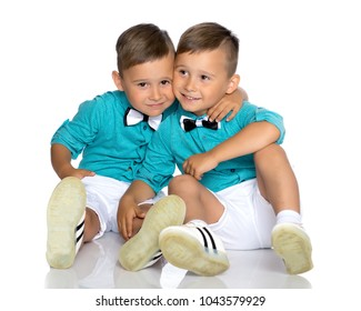 Two cute little boys, brothers sit on the floor in a studio on a white background. The concept of a happy childhood, the development of a child in the family. Isolated.