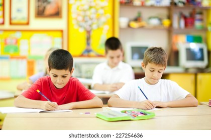 Two cute little boys sitting in the classroom and writing. Elementary age. Other kids in the background. NOTE: All the drawings and artwork in the classroom are made by children.