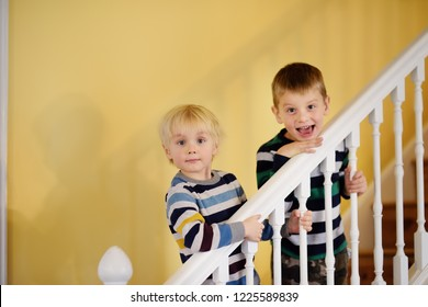Two cute little boys in striped jumpers on the stairs in the house. Child friendship concept.