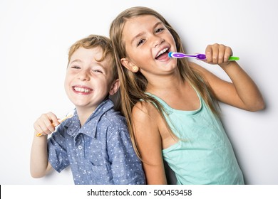 Two Cute little child brushing teeth, isolated on white