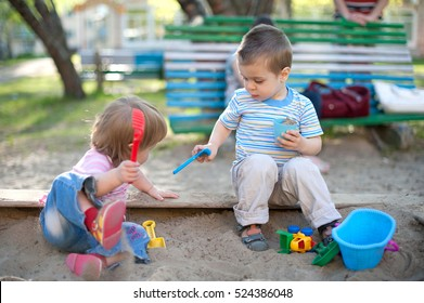 Two cute little children brother and sister playing in a sandbox