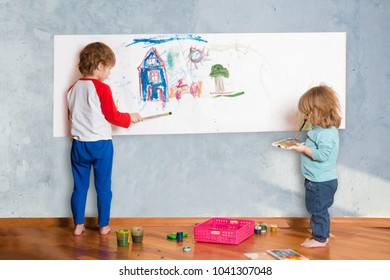 two cute little children painting on the  paper on wall in room