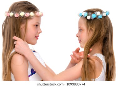 Two cute little girls close-up, in the studio on a white background. The concept of a happy childhood, Beauty and fashion. Isolated.