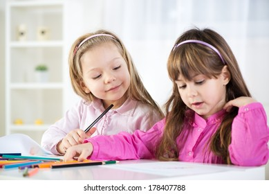 Two cute little girls drawing with colored pencils at home.